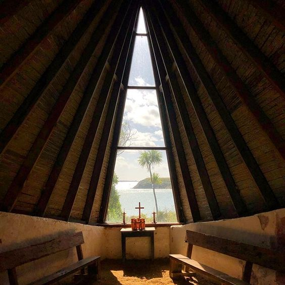 Image of the unique chapel at Quarantine Island. The small building is shaped like the upturned hull of a boat, the window is a tall triangle and frames a view looking toward the Otago Harbour heads.