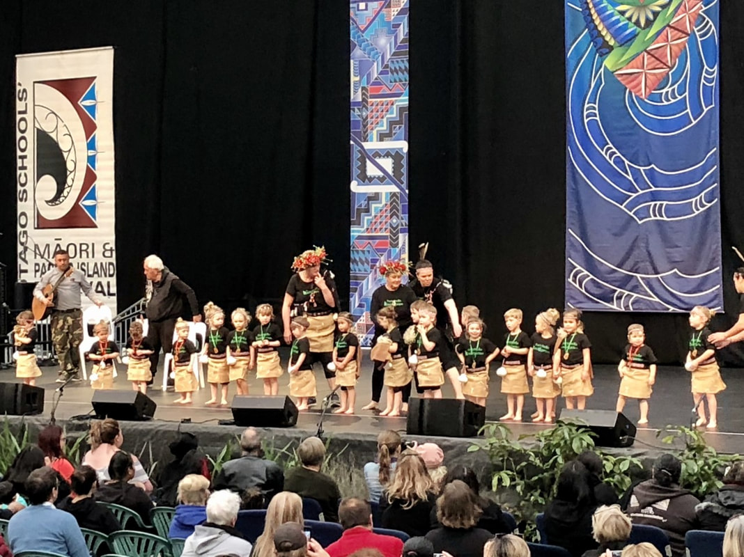 Emily Larkins Author's youngest daughter's Otago Polyfest 2019 group on stage in traditional costume. Click the image to watch and hear her performance at 3:22:00.