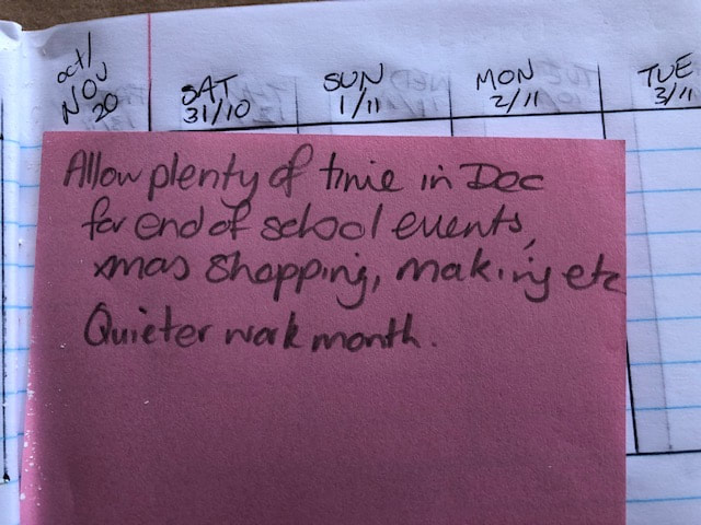 Image from Emily's planner showing a pink memo cube sheet tucked in to remind her to plan a quieter month in December.
