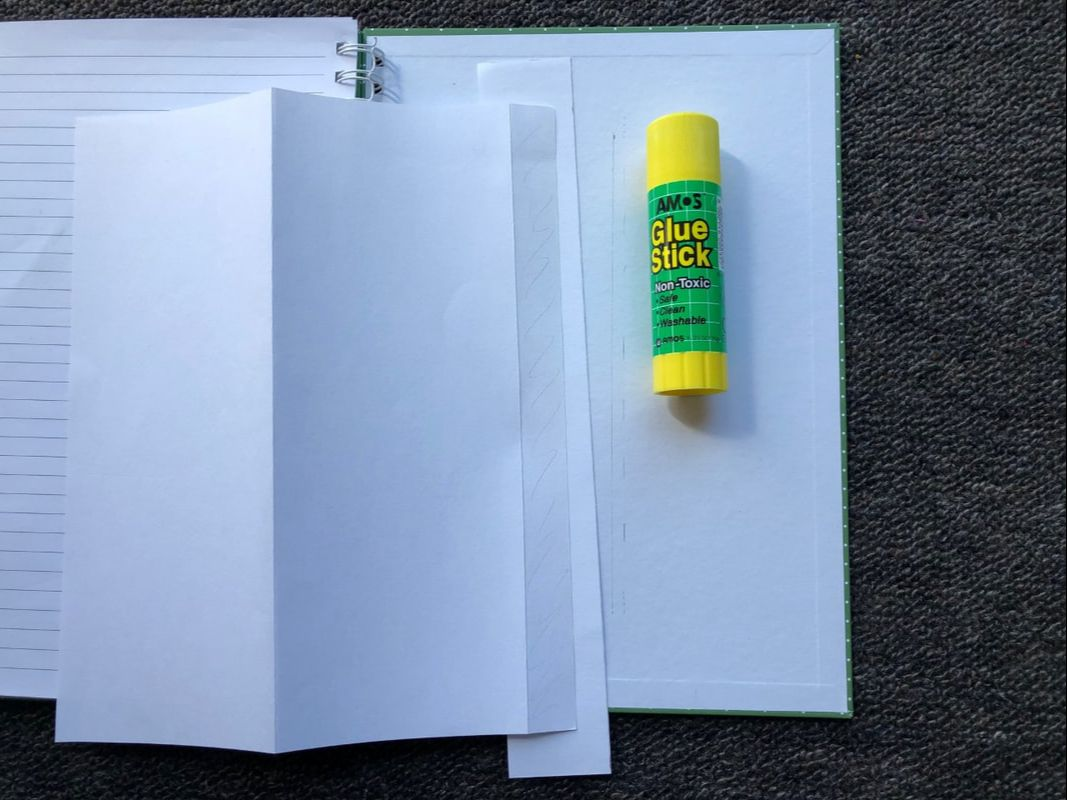 Illustrating gluing the attachment tab with scrap paper underneath to prevent unwanted glue marks on journal cover.